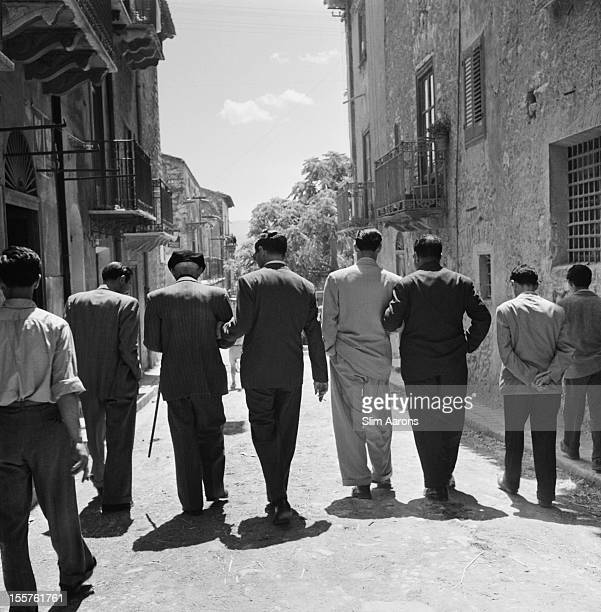 Mafia boss Charles 'Lucky' Luciano walking with his henchmen with their backs to the camera in Sicily Italy 31 December 1948 Luciano assists one of...