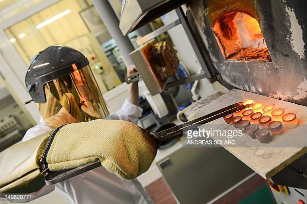 IDE Mafia cashes in as hardup Italians flog their gold A metal worker holds a bowl during the melting of silver for the realization of a gold bar at...