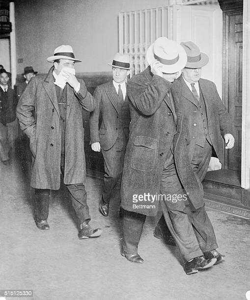 Mafia leader Al Capone and his bodyguard Frank Cline hide their faces as they are escorted by police detectives Creedon and Malone after they were...