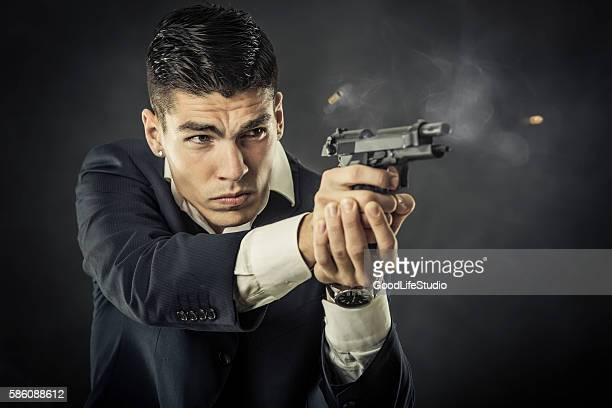 mafia man shooting a gun - man on fire stock photos and pictures
