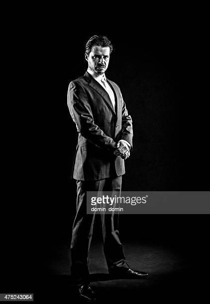 Mafioso, gangster, man in full suit, slicked back hair, displeased