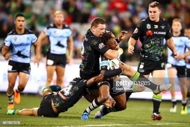 Mafoa'aeata Hingano and Shannon Boyd of the Raiders tackle James Segeyaro of the Sharks during the round 10 NRL match between the Canberra Raiders...