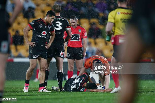 Mafoa'aeata Hingano of the Warriors receives medical attention on his ankle as Roger TuivasaSheck looks on during the round 23 NRL match between the...