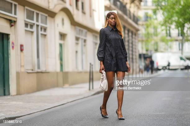 Magalie Kab wears a hair clip, a gathered black mini dress with shirt collar, a white leather bag, black high heels pointed pumps shoes, on May 03,...