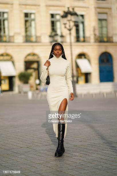 Magalie Kab wears earrings, a white wool turtleneck long slit dress, a black leather bag with pearls, black leather knee-high combat boots, on March...
