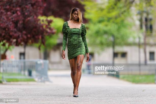 Magalie Kab wears gold earrings, a green with white spots straight neck puffy shoulder long sleeves short laces dress, black shiny leather pointed...
