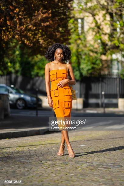 Magalie Kab wears long earrings, an off-shoulder orange dress with six attached pockets, a yellow grid bag, sandals, on March 28, 2021 in Paris,...