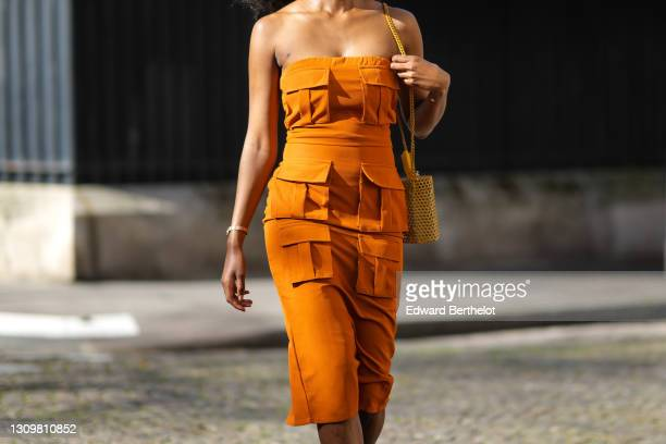 Magalie Kab wears long earrings, an off-shoulder orange dress with six attached pockets, a yellow grid bag, on March 28, 2021 in Paris, France.