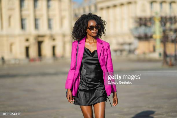 Magalie Kab wears sunglasses, a neon purple blazer jacket, a black short shiny satin / silky dress, a blue bejeweled bag, on March 31, 2021 in Paris,...