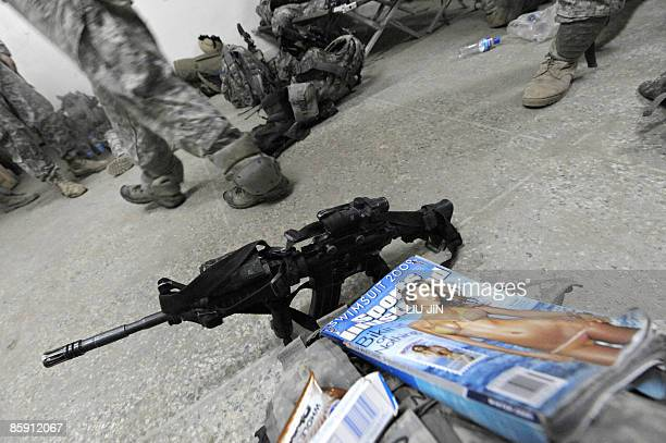 A magazine is seen next to a US soldier's M4 assault rifle at an operation post in Nishagam in Afghanistan's eastern Kunar province on April 10 2009...