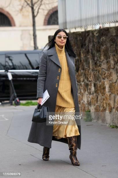 Magazine publisher and director of Tank magazine Caroline Issa wears Ray Ban sunglasses, a grey coat, yellow polo neck jumper, yellow silk skirt,...