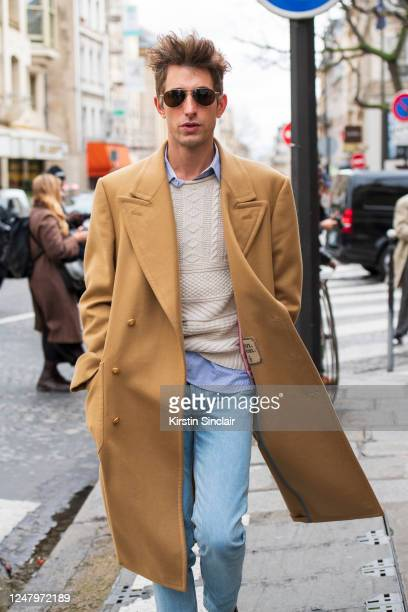 Magazine style director David Thielebeule wears an 8oave Amour coat, blue jeans and a cream jumper on February 29, 2020 in Paris, France.