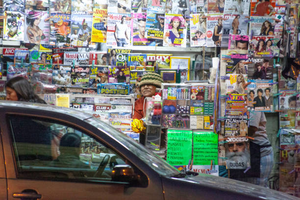 A magazine vendor is in the middle of a mixed magazine stand