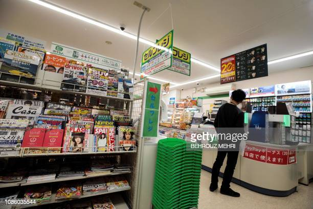 Magazines are pictured on the shelf of a convenience store in Tokyo on January 22 2019 Japan's omnipresent convenience stores are preparing to stop...