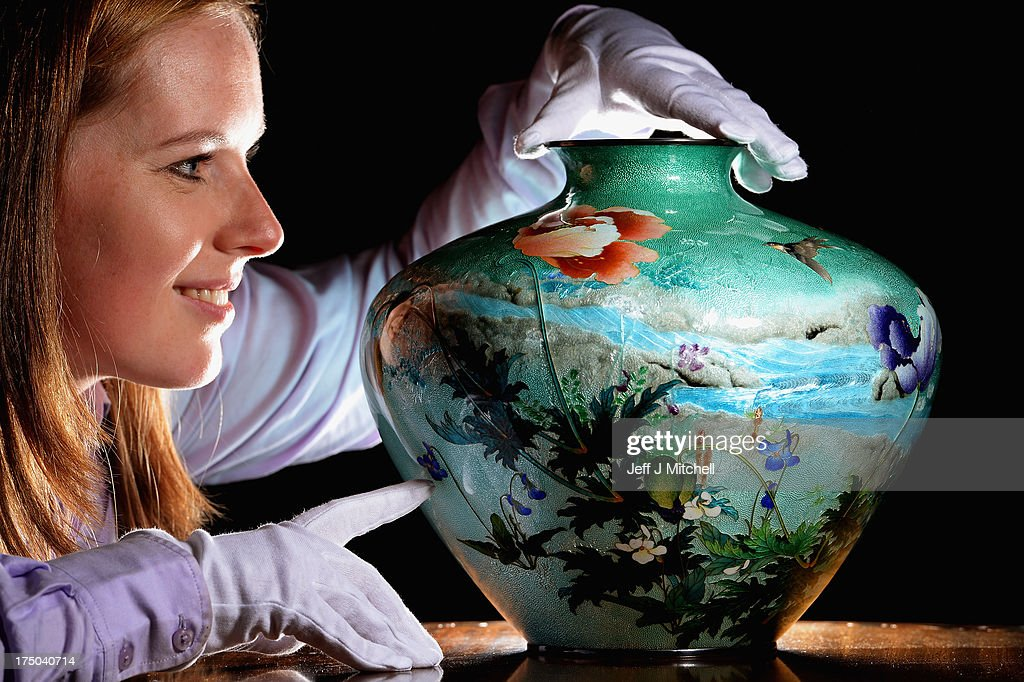 Magda Ketterer, East Asian Works of Art Specialist views a unique Japanese vase made by renowned Japanese artist Kumeno Teitaro, sold for GBP £17,000 in McTears Asian Works of Art sale on July 30, 2013 in Glasgow, Scotland. The vase is an example of Teitaro's famous technique of transparent enamel applied over design in silver. The vase was previously part of Lord and Lady Wark's collection, and has been passed down over the years to the current owner, who has had it in his Glasgow home for some time. Photo by Jeff J Mitchell/Getty Images)