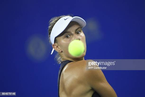Magda Linette of Poland hits a return against Garbine Muguruza of Spain during their third round women's singles match at the WTA Wuhan Open tennis...