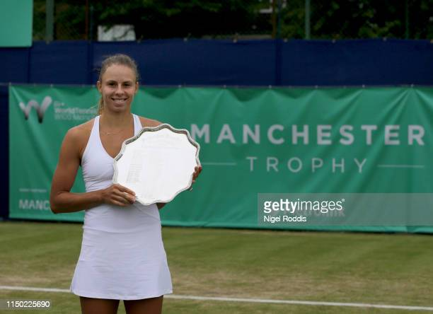 Magda Linette of Poland poses for pictures after winning the Women's singles Final of the Manchester Trophy against Zarina Diyas of Kazakhstan at The...