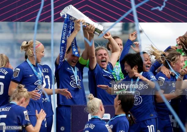 Magdalena Eriksson and Millie Bright of Chelsea lift the Barclays FA Women's Super League Trophy as their team mates celebrate after the Barclays FA...