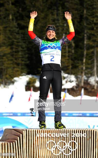 Magdalena Neuner of Germany celebrates gold during the flower ceremony for the women's 12.5 km mass start biathlon on day 10 of the 2010 Vancouver...