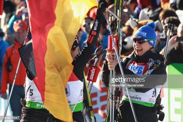 Magdalena Neuner of Germany celebrates winning at the finsih area of the Women's 4 x 6km Relay with her team mate Andrea Henkel during the IBU...