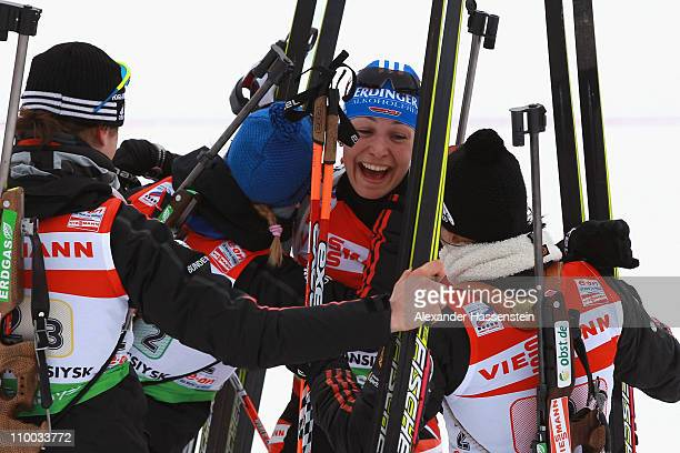 Magdalena Neuner of Germany celebrates winning the gold medal with her team mates Andera Henkel Miriam Goessner and Tina Bachmann at the finish area...