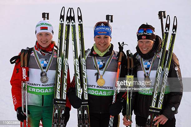 Magdalena Neuner of Germany poses with Darya Domracheva of Belarus and Tora Berger of Norway at the medal ceremony for the women's mass start during...