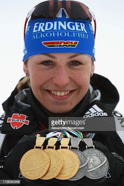 Magdalena Neuner of Germany poses with her gold medal for the women's 75km sprint gold medal for the women's mass start gold medal for the women's...