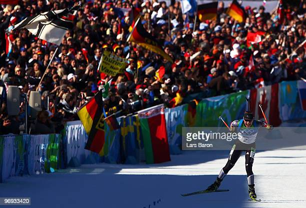 Magdalena Neuner of Germany skies to the line to claim gold in the women's biathlon 12.5 km mass start on day 10 of the 2010 Vancouver Winter...