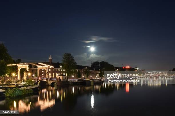 Magere Brug and Walter Suskindbrug illuminated at night with reflection and full moon in Amsterdam