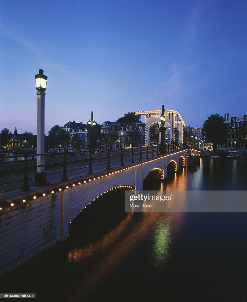 Magere brug bridge (Skinny Bridge) on Amstel river illuminated at dusk : Foto stock