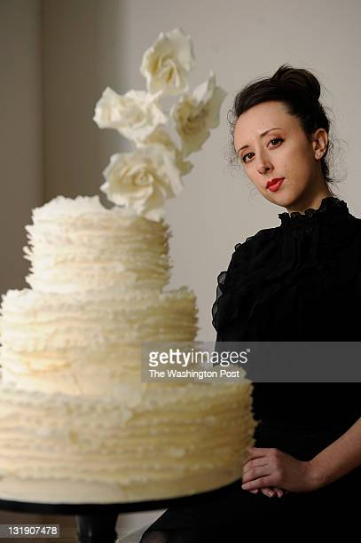 Maggie Austin LaBaugh of Maggie Austin Cake poses for a portrait with a three tier ivory frill cake with sugar roses at her new location on Thursday...