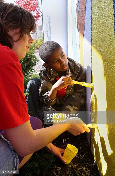 Maggie Casey from the Dorchester Youth Council and Adam Butler of Mattapan paint a mural to promote awareness and participation in the 2010 census at...