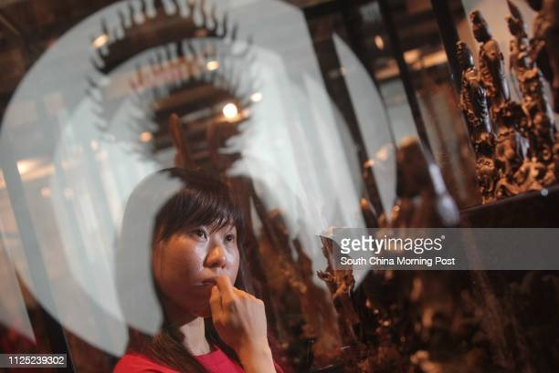 Maggie Cheng staff of Champion Technology Group and Chinese World Cultural Heritage looking at the Agarwood during the Opening ceremony and media...
