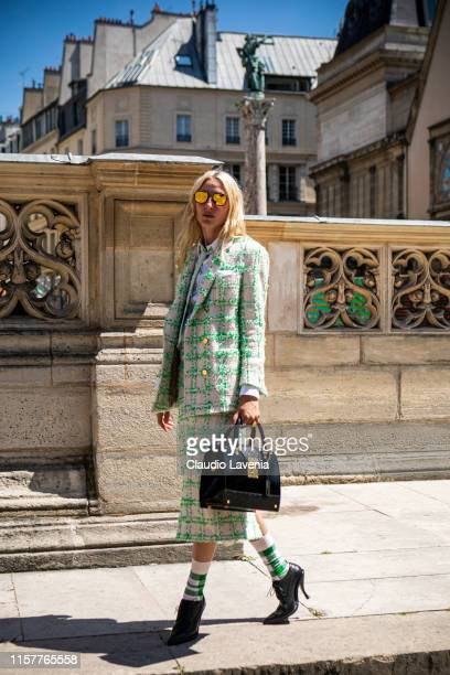 Maggie Maurer wearing a green and cream decorated blazer with matching skirt white shirt green striped necktie green and white socks black heels and...