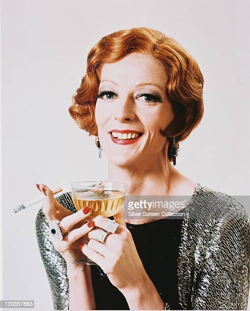 Maggie Smith British actress smiling in a studio portrait weaing a black top beneath a silverandblack cardigan holding a lit cigarette and a...