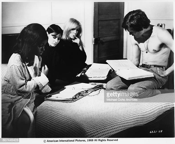 Maggie Thrett Judy Pace Yvette Mimieux and Christopher Jones sit on a bed and read on set of the movie Three in the Attic circa 1969