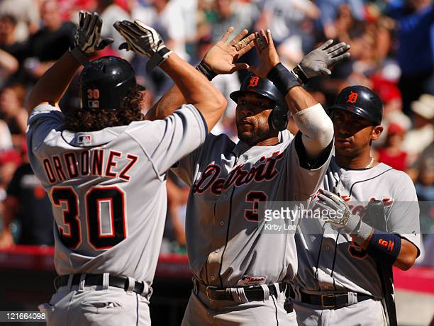 Magglio Ordonez of the Detroit Tigers is greeted by teammates Gary Sheffield and Carlos Guillen after hitting a tworun homerun in the ninth inning of...