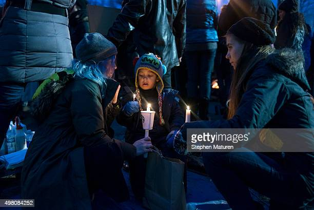 Magic Baumgartner left her child Noble Baumgartner and Moly Glasgow hold candles and listen to speeches at a candlelight vigil held for Jamar Clark...