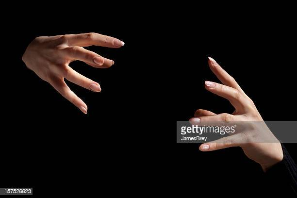 magic fingers; two intense hands hold nothing inbetween, black background - goochelaar stockfoto's en -beelden