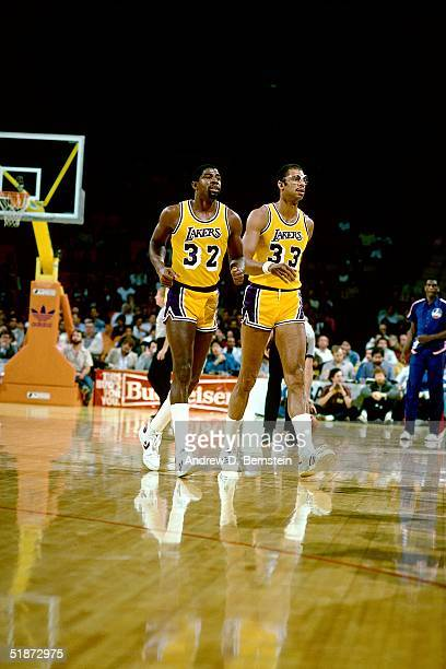 Magic Johnson and Kareem AbdulJabbar of the Los Angeles Lakers walk off the court during the NBA game against the New Jersey Nets at the Forum in Los...