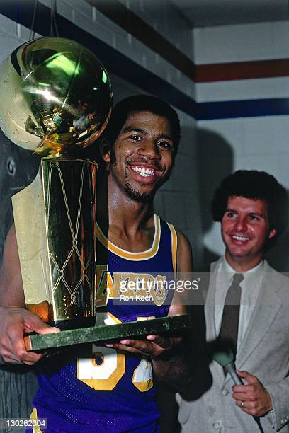 Magic Johnson of the Los Angeles Lakers celebrates with the trophy after winning the NBA Championship during Game Six of the 1985 NBA Finals on June...