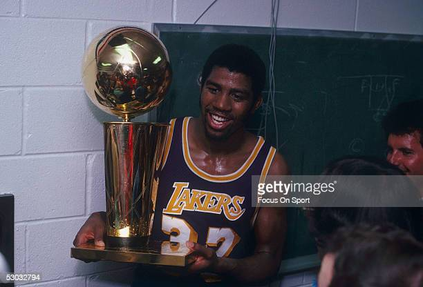 Magic Johnson of the Los Angeles Lakers celebrates with the Walter A. Brown championship trophy after winning Game 6 and the series against the...