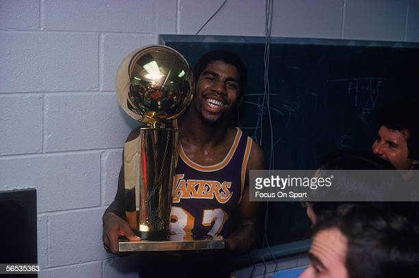 Magic Johnson of the Los Angeles Lakers celebrates with the Walter A Brown championship trophy after winning Game 6 and series against the...