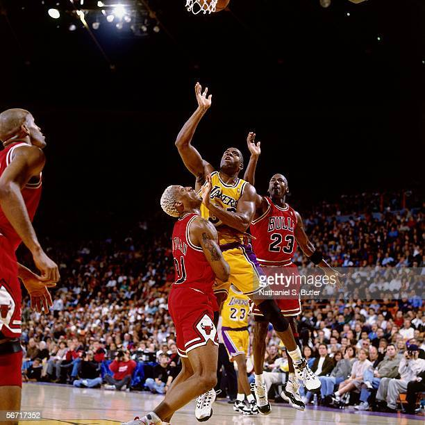 Magic Johnson of the Los Angeles Lakers drives to the basket against Dennis Rodman and Michael Jordan of the Chicago Bulls during an NBA game at the...