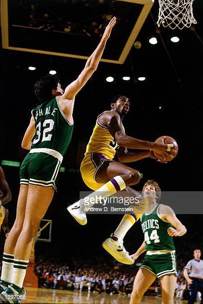 Magic Johnson of the Los Angeles Lakers drives to the basket for a layup against the Boston Celtics during an NBA game at the Forum in Los Angleles...