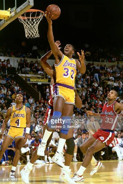 Magic Johnson of the Los Angeles Lakers goes for a layup against the Los Angeles Clippers during the NBA game at the Forum in Los Angeles California...