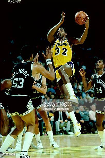 Magic Johnson of the Los Angeles Lakers goes for a layup against the San Antonio Spurs during the NBA game at the Forum in Los Angeles California...