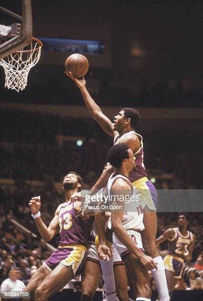 Magic Johnson of the Los Angeles Lakers jumps to shoot against the New York Knicks as teammate Kareem Abdul Jabbar watches at Madison Square Garden...