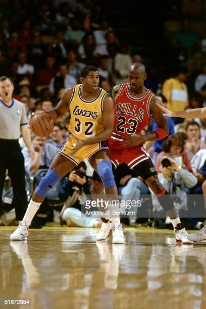 Magic Johnson of the Los Angeles Lakers looks to make a play while Michael Jordan of the Chicago Bulls defends during Game Five of the 1991 NBA...