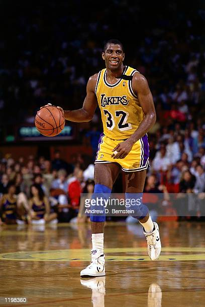 Magic Johnson of the Los Angeles Lakers moves the ball upcourt during an NBA game at the Forum in Los Angeles California NOTE TO USER User expressly...